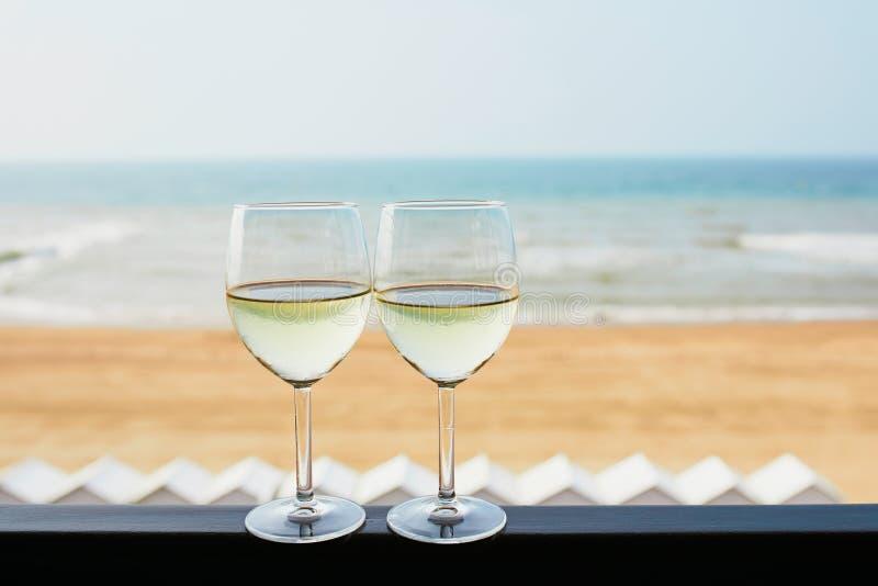 Due vetri di vino bianco con la costa atlantica tirano nel fondo fotografie stock libere da diritti