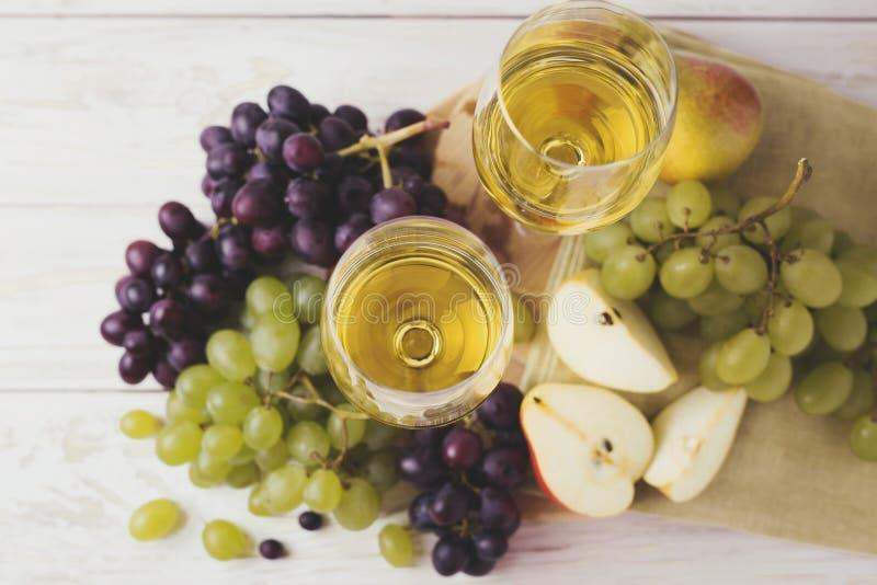 Due vetri di vino bianco, dell'uva fresca e della pera fotografia stock