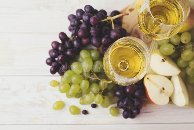 Due vetri di vino bianco, dell'uva fresca e della pera fotografia stock libera da diritti
