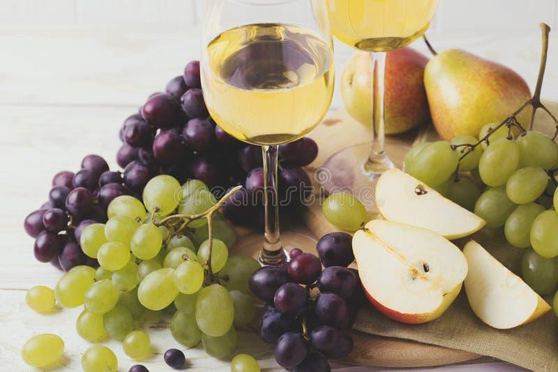 Due vetri di vino bianco, dell'uva fresca e delle pere immagini stock