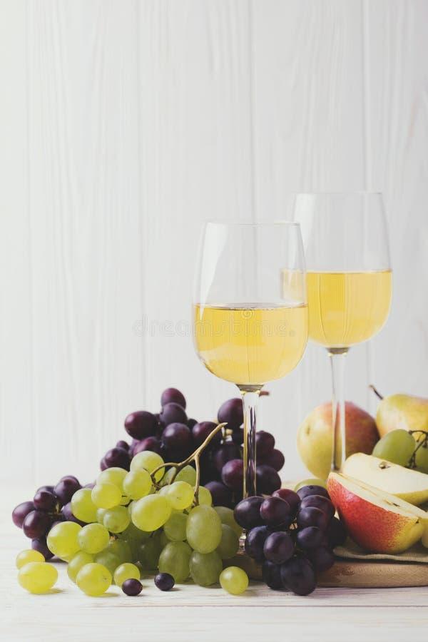 Due vetri di vino bianco, dell'uva fresca e delle pere immagine stock libera da diritti