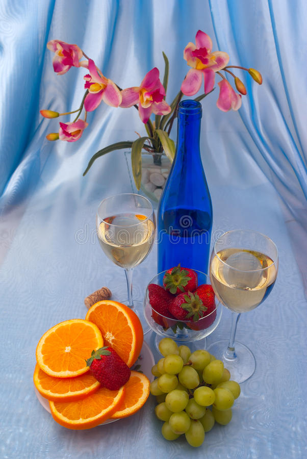Due vetri di vino bianco e della bottiglia blu con l'orchidea immagini stock