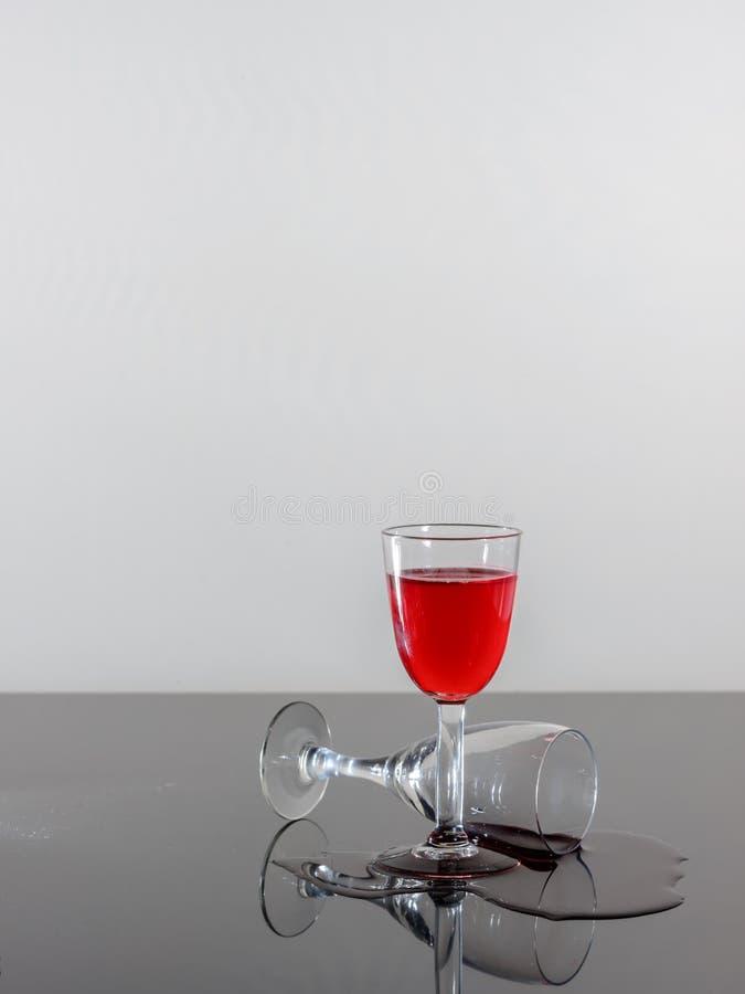 Due vetri di vino d'annata e un certo vino rovesciato su una superficie riflettente fotografia stock