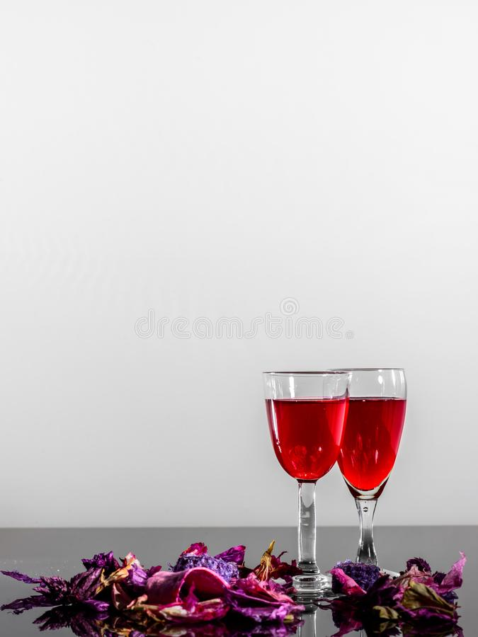 Due vetri di vino d'annata ed alcuni petali su una superficie riflettente immagini stock