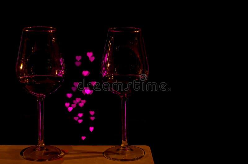 Due vetri di vino rosso affinchè una coppia celebrino San Valentino con il bokeh di forma di amore fotografia stock libera da diritti