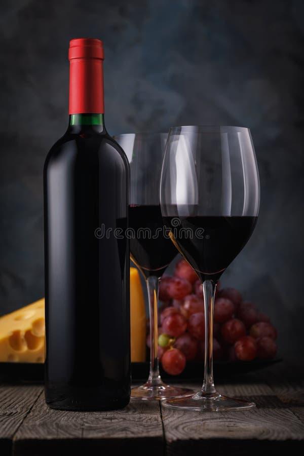 Due vetri di vino rosso con formaggio e l'uva su una tavola di legno immagine stock