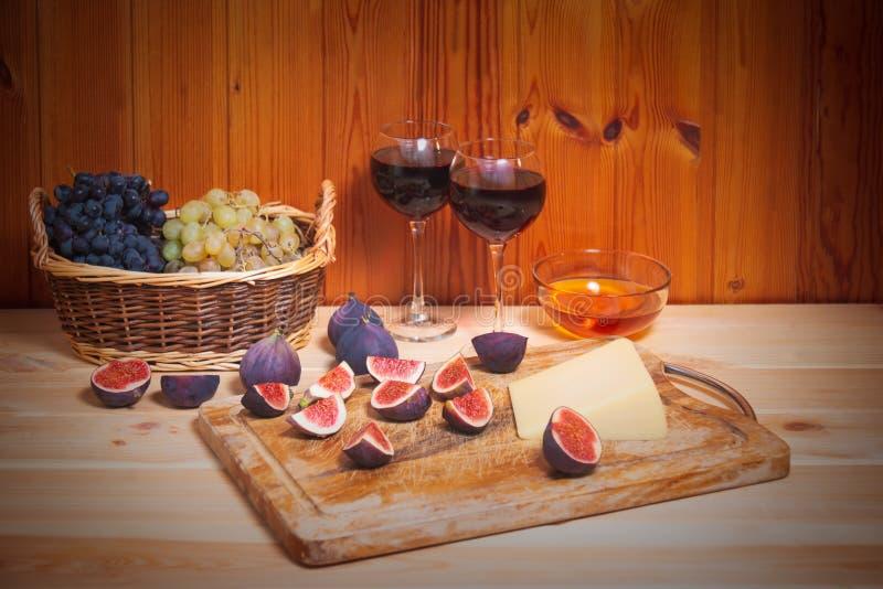Due vetri di vino rosso, dei fichi, del formaggio, dei mazzi di uva e della ciotola di miele sulla tavola di legno fotografie stock