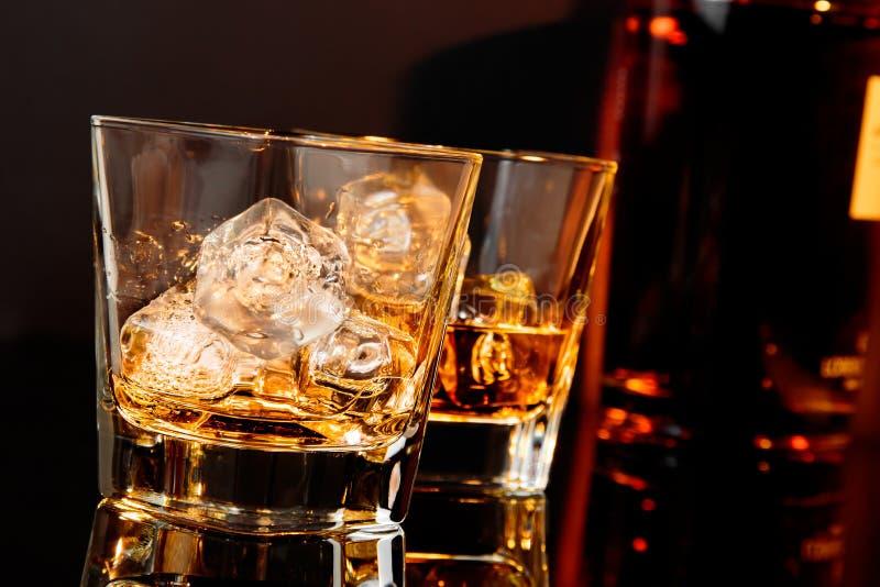 Due vetri di whiskey davanti alla bottiglia di whiskey immagine stock