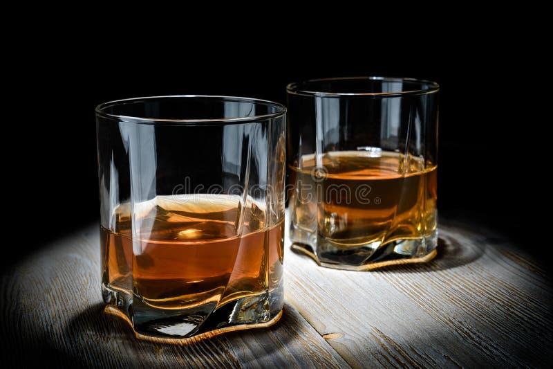 Due vetri di whiskey su una tavola di legno d'annata su un fondo nero immagini stock libere da diritti