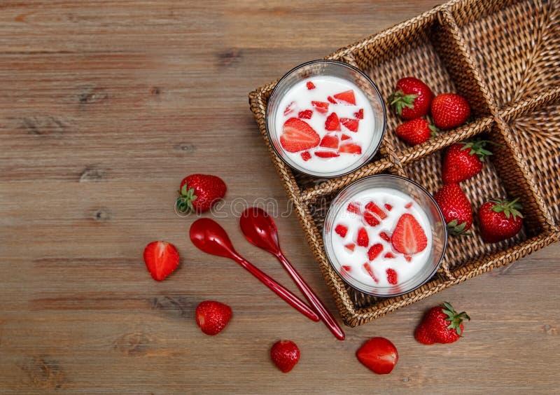 Due vetri di yogurt, fragole fresche rosse nel contenitore di rattan con i cucchiai di plastica sulla Tabella di legno Prima cola immagini stock
