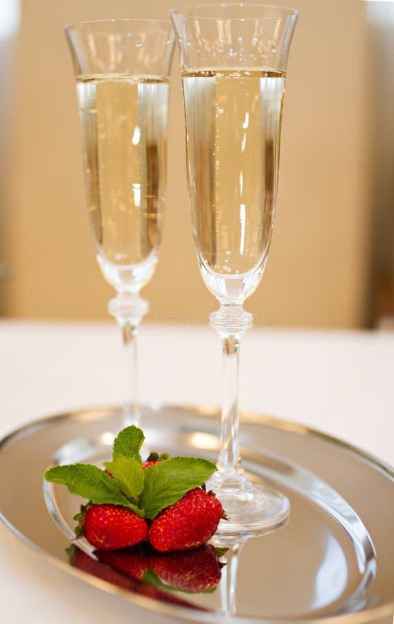 Due vetri e fragole del champagne isolati su bianco fotografia stock libera da diritti