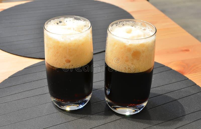Due vetri pieni a metà di birra nera sul dettaglio della tavola fotografie stock libere da diritti