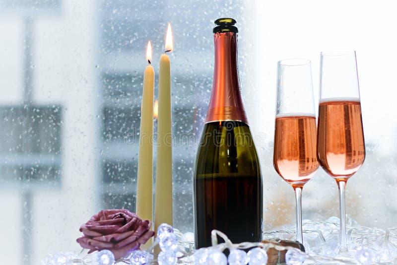Due vetri riempiti, candele e una bottiglia fotografia stock