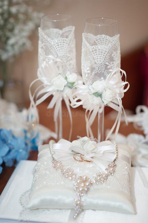 Due vetri wedding Un bello insieme degli accessori di nozze per la sposa Collana ed anelli della perla della sposa di mattina sul fotografie stock