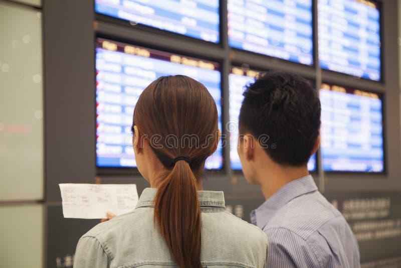 Due viaggiatori che esaminano gli schermi di partenza di volo l'aeroporto fotografie stock libere da diritti