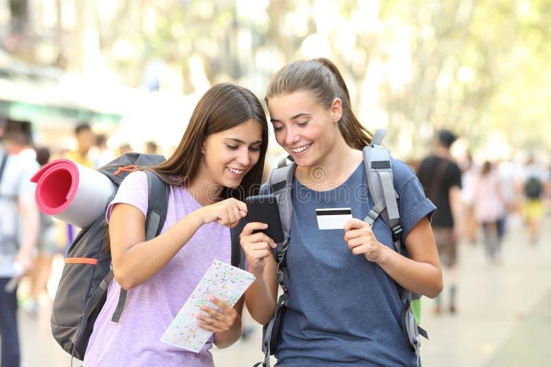 Due viaggiatori con zaino e sacco a pelo che cercano contenuto online immagine stock libera da diritti