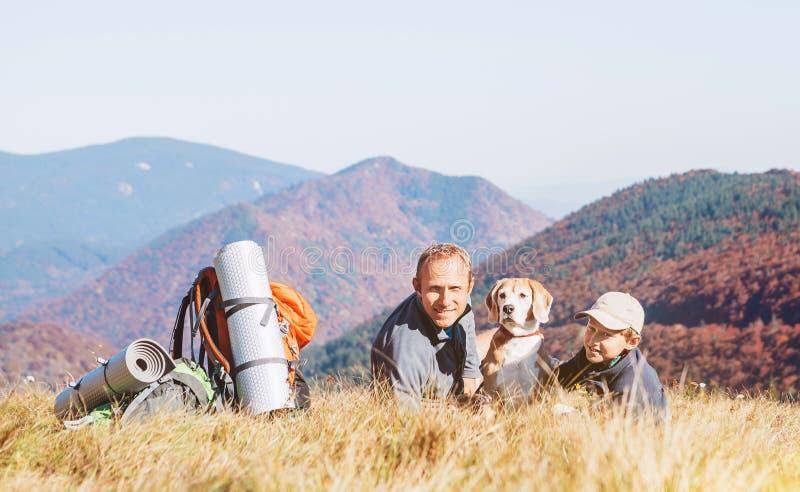 Due viaggiatori con zaino e sacco a pelo generano e le viandanti del figlio riposano su spirito della collina della montagna fotografia stock