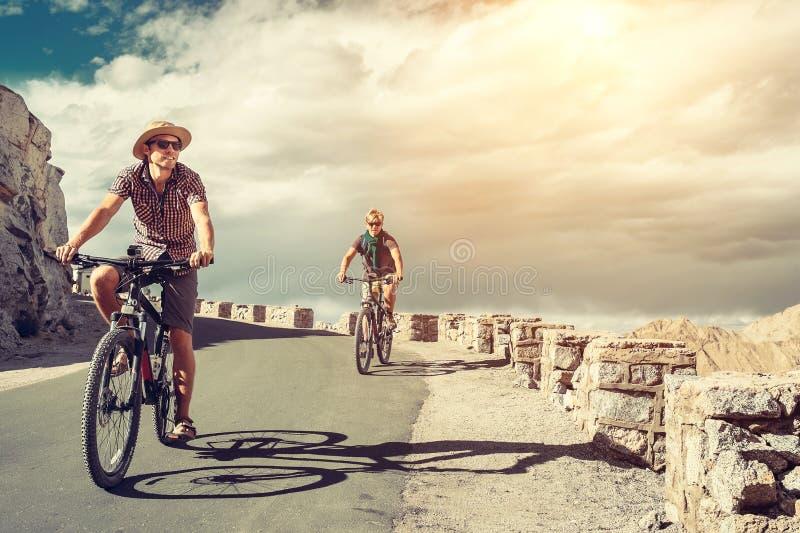 Due viaggiatori del bicykle sulla strada della montagna in Himalaya fotografie stock