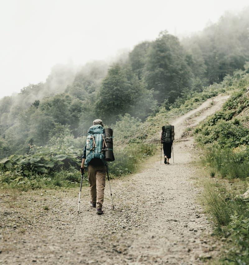 Due viandanti che camminano sul percorso in montagne fotografia stock