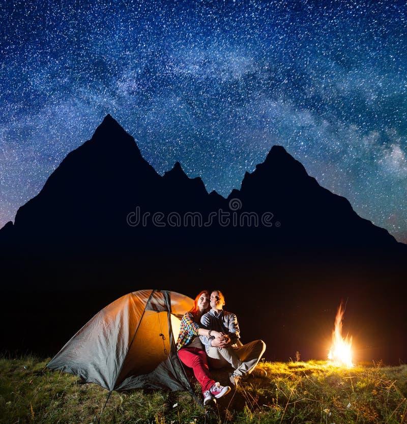 Due viandanti che hanno un resto nel suo campo alla notte vicino a fuoco di accampamento sotto splende il cielo stellato immagine stock libera da diritti