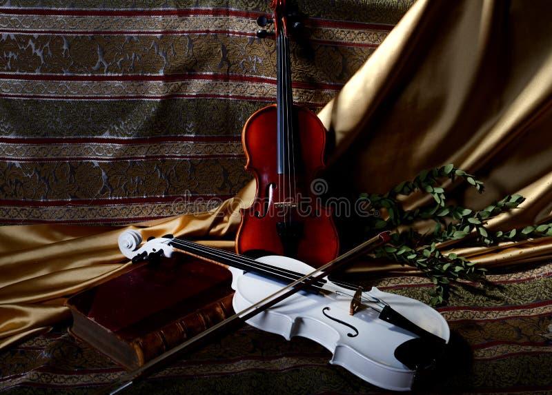 Due violini su un fondo del tessuto con un arco e un libro fotografie stock