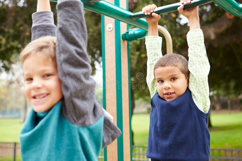 Due Young Boys sulla struttura di scalata in campo da giuoco immagini stock