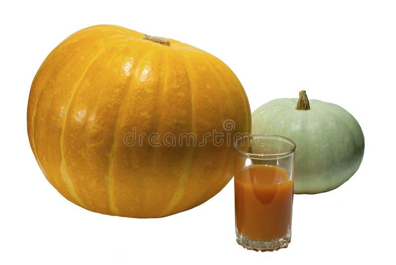 Due zucche e un vetro del succo della zucca isolato fotografia stock libera da diritti