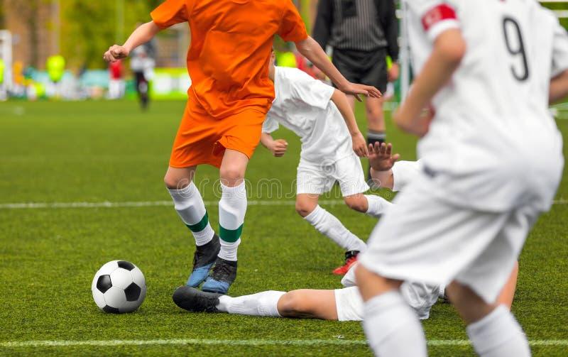 Duelo del fútbol Jugadores corrientes jovenes que compiten para el balón de fútbol imagen de archivo