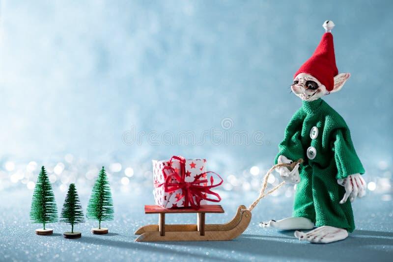 Duende alegre lindo del ayudante de Santas que tira del trineo de Santas con el regalo de Navidad Escena de la Navidad de Polo No fotografía de archivo libre de regalías