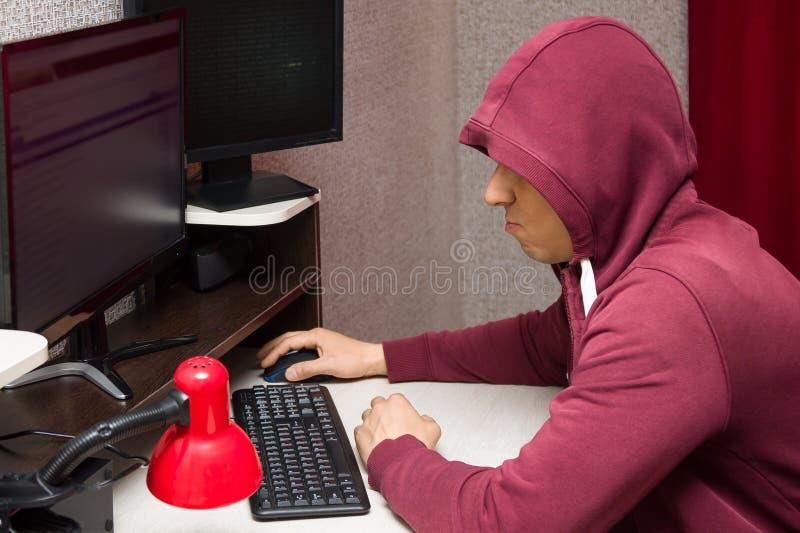 Duende de Internet usando el ordenador Hombre malo y feo que escribe cosas desagradables en el foro imagenes de archivo