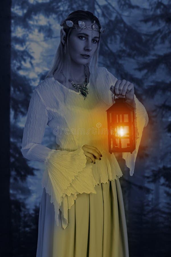 Duende femenino del retrato alto con la linterna en la noche fotografía de archivo libre de regalías
