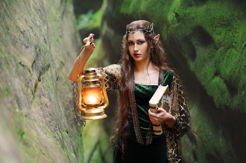 Duende femenino hermoso joven que camina a través del bosque con un abucheo imágenes de archivo libres de regalías