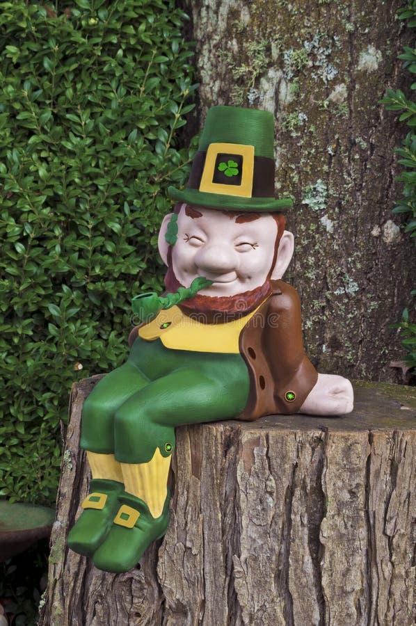 Duende que sonríe y que se sienta en tronco de árbol con el tubo imagenes de archivo