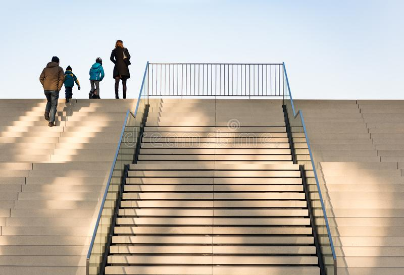 DUESSELDORF, GERMANY - JANUARY 22, 2017: An unidentified family is climbing the staircase on the side of the Hyatt hotel stock photography