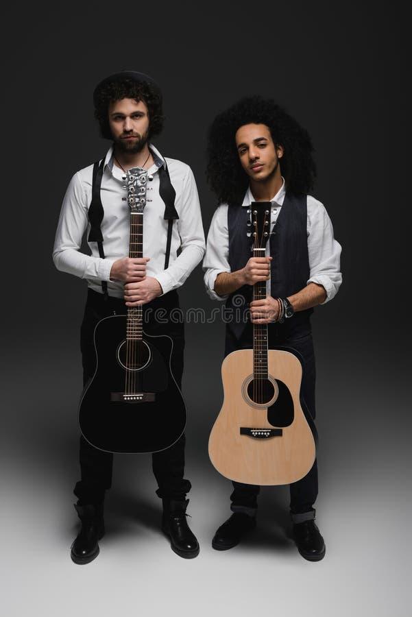 duet przystojni młodzi muzycy z gitarami akustycznymi obraz stock