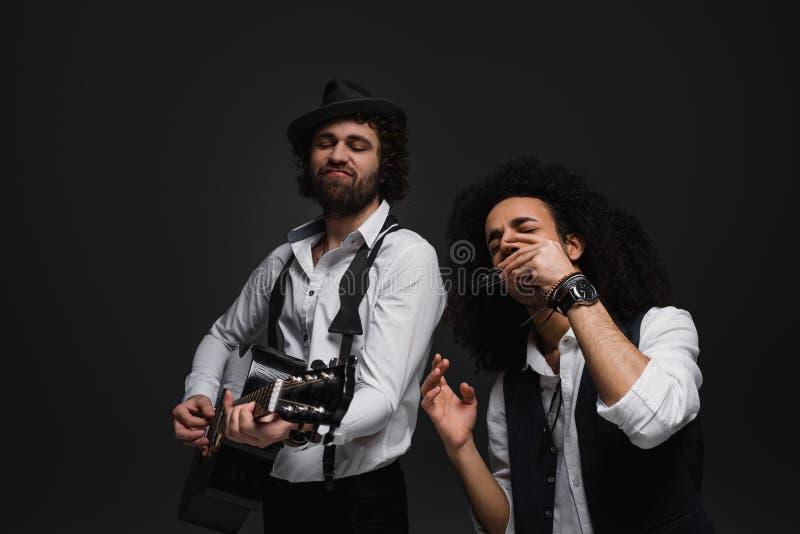 dueto dos músicos expressivos que jogam a guitarra acústica e a harmônica fotos de stock