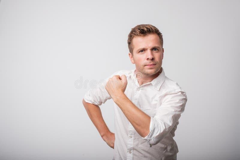 Dufny w średnim wieku mężczyzna w białej koszula z zaciskającą pięścią obrazy stock