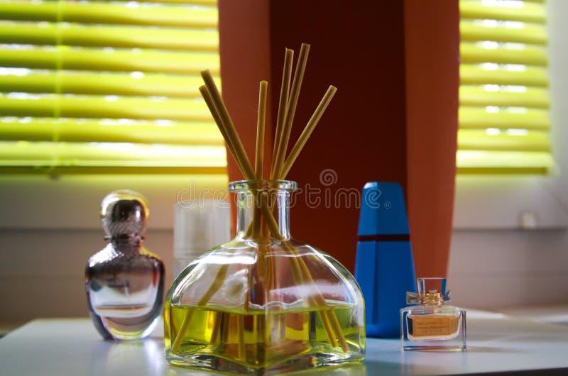 Duftbelüfterglas mit Reedstöcken zwischen Parfüm flacons, die natürlichen Geruch der Zitrone geben stockfotos