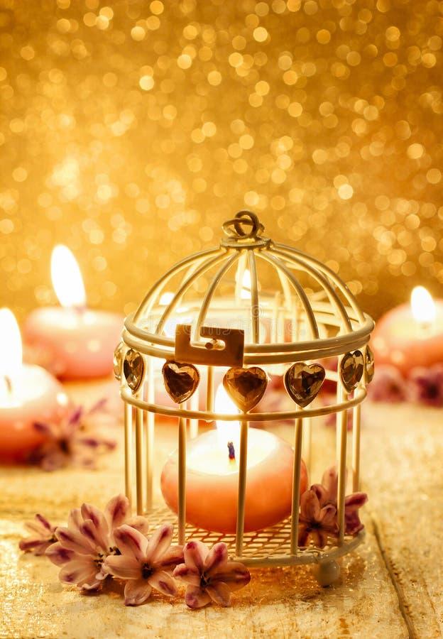 Duftende Kerze in Weinlese Birdcage. Goldener Hintergrund stockfotografie