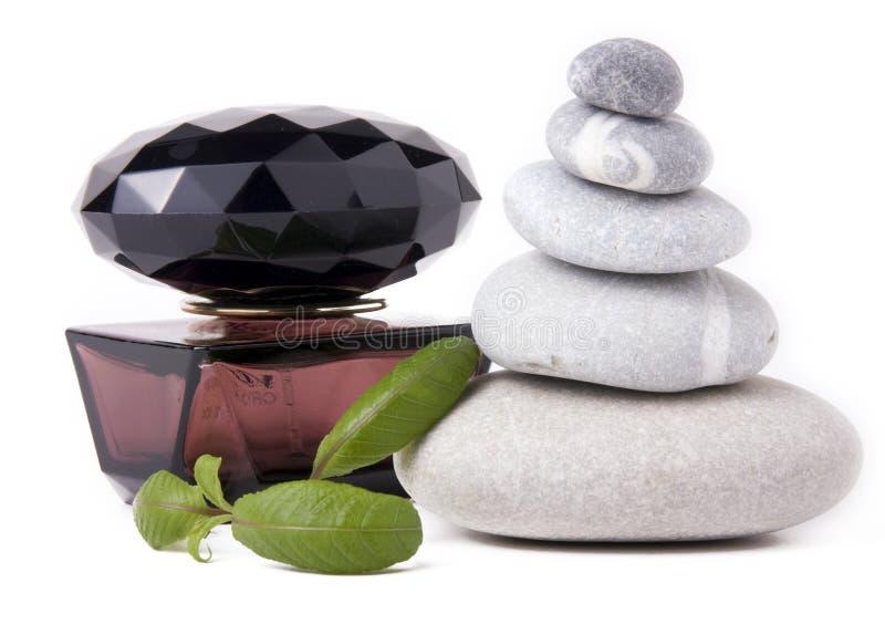 Duftstoff, Steine und grüne Blätter lizenzfreies stockbild