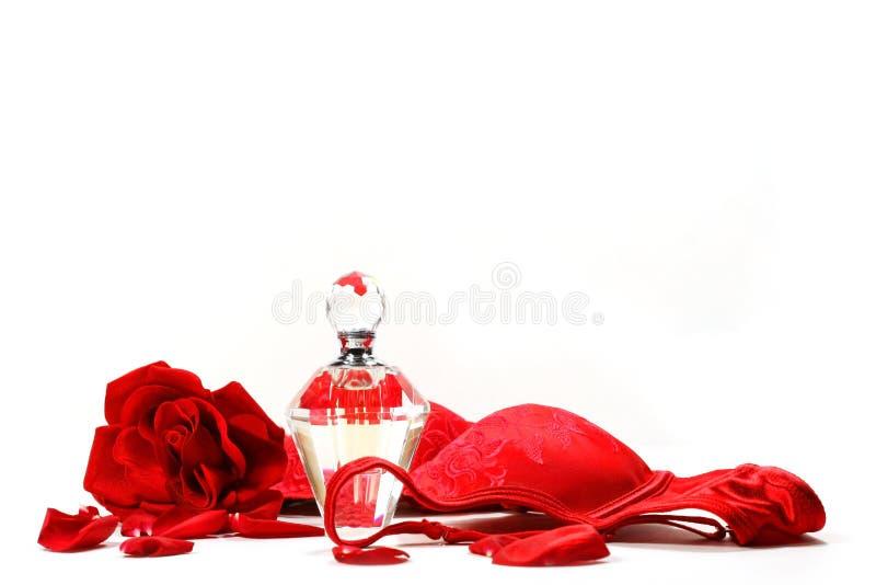 Duftstoffflasche, Rose und roter Büstenhalter stockfotografie