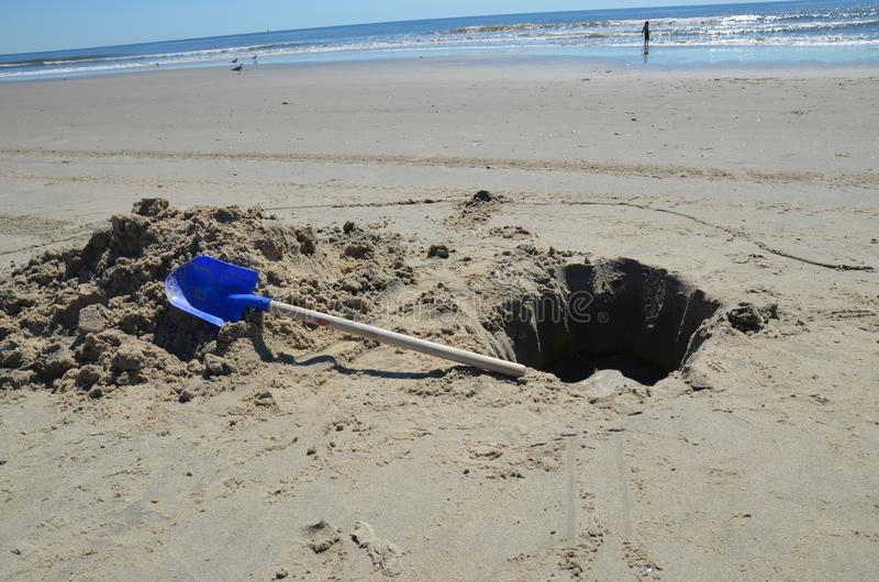 Dug hole on the beach with a blue shovel. A hole dug on the beach and left behind with a blue shovel and the ocean in the background royalty free stock photo