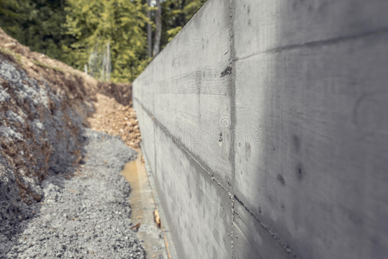 Dug out shaft next to a newly build concrete wall outside in a h. Ome garden to form a border between two properties stock photography