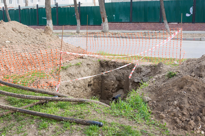 Dug pit fenced for replacing electric cables. Underground royalty free stock photo