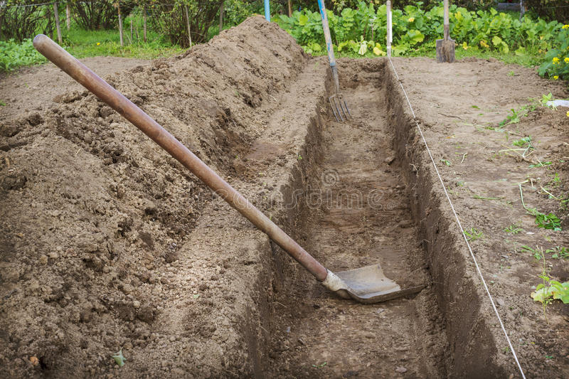 Dug a trench to arrange a deep bed of. Dug a trench in the garden to make a deep bed of royalty free stock photography