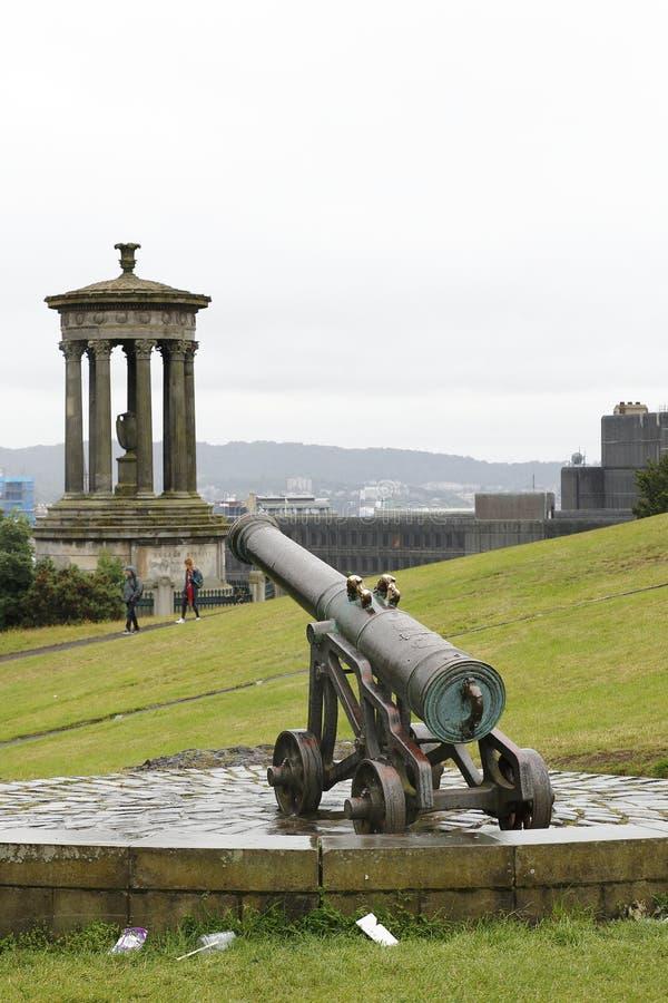 Dugald Stewart Monument e canhão no monte de Calton, montanha em Edimburgo no leste de Escócia foto de stock royalty free
