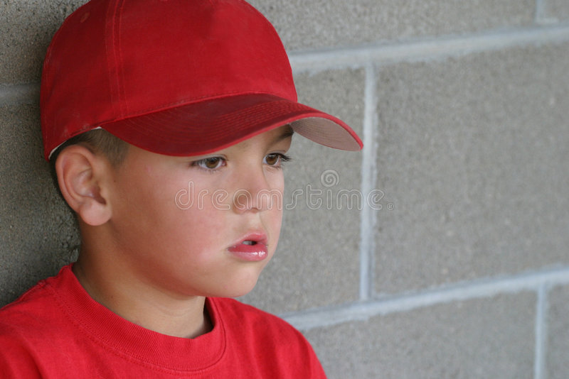 In The Dugout. A young Hispanic Native American boy with a very pouty face sits in the dugout waiting to get back into the game. Shallow depth with selective royalty free stock photo
