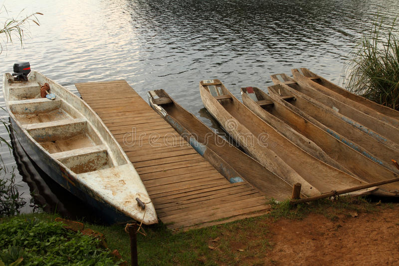 Dugout Canoes waiting at the Dock. A group of Dugout canoes and one boat launch waiting on a lake shore at the dock stock photos