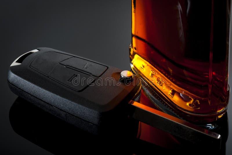Dui-, DWI-, Alkohol- im Strassenverkehr und Alkoholismuskonzept mit Autoschlüsseln nahe bei einer Flasche Schnapswhisky, Rum, Wei lizenzfreie stockfotografie