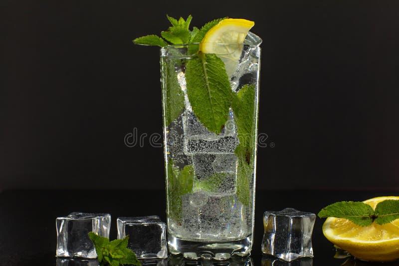 Duidelijk water in glas met groene muntbladeren en ijsblokjes op zwarte achtergrond stock afbeeldingen